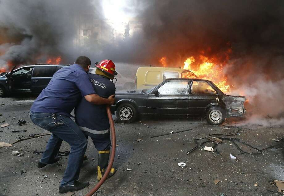 Helping hand: A man steadies a firefighter hosing down flames after a car bombing in Beirut's   southern suburb of Bir al-Abed. Dozens were wounded in the blast. Photo: -, AFP/Getty Images