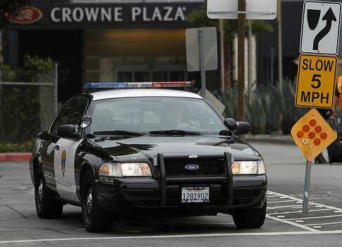 A police officer leaves the parking lot where security personnel limit access to the Crowne Plaza Hotel in Burlingame, Calif. on Tuesday, July 9, 2013, where the parents of passengers from Asiana Airlines flight 214 are reportedly staying. Photo: Paul Chinn, The Chronicle