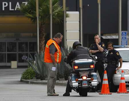 A security guard checks the identification of a motorcyclist arriving at the Crowne Plaza Hotel in Burlingame, Calif. on Tuesday, July 9, 2013. Access to the hotel is restricted, where the parents of passengers from Asiana Airlines flight 214 are reportedly staying. Photo: Paul Chinn, The Chronicle