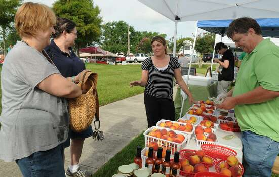 Cassie Mitchel, center, chats with NJ Coffman, from left, of Rosharon and Sandy White, of Pearland who check out the peaches of Charlie Hester, right, of the Bay Area and South Star of Texas during the Pearland Old Townsite Farmers Market at Zychlinski Park.  Photo: Jerry Baker, Freelance