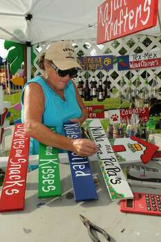 Marti Thibodeaux of League City gets ready to open for business at the Pearland Old Townsite Farmers Market at Zychlinski Park.  Photo: Jerry Baker, Freelance