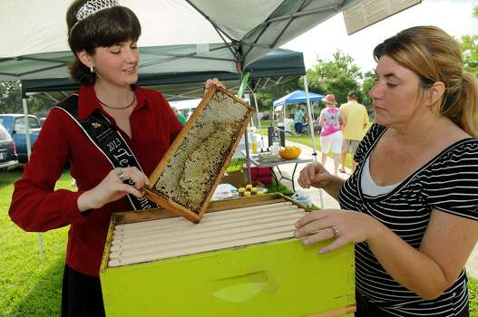 Texas Honey Queen Shelby Kilpatrick, left, a freshman at Texas A&M University majoring in entomology, explains the workings of a beehive to Cassie Mitchel during the Pearland Old Townsite Farmers Market at Zychlinski Park. Photo: Jerry Baker, Freelance