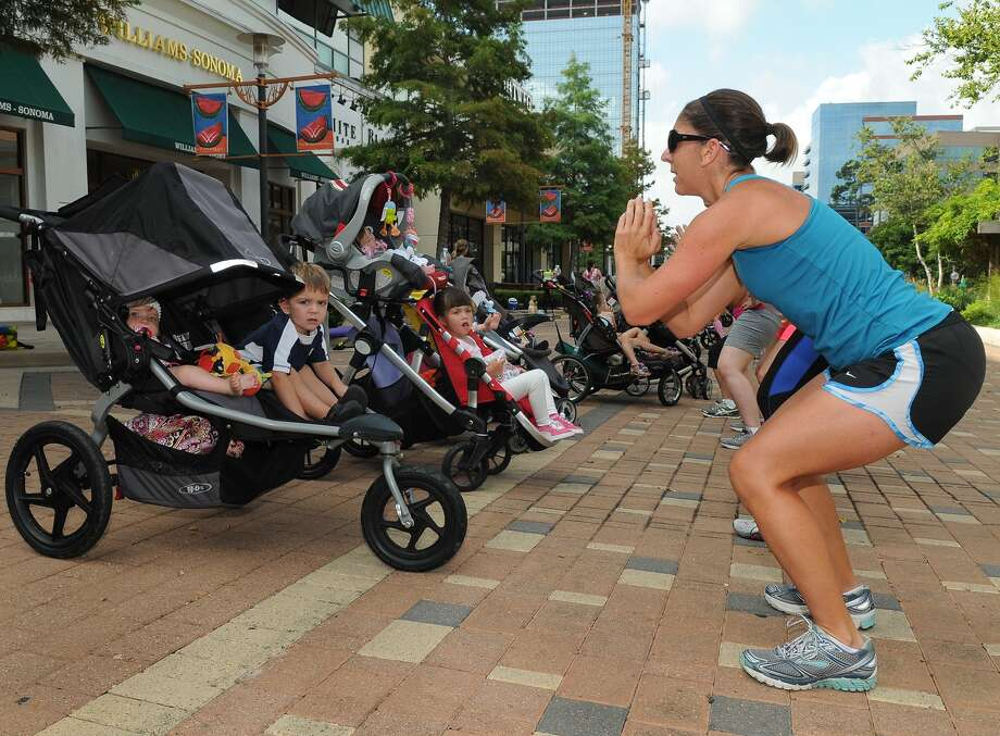Lisa Ducote and her Baby Boot Camp classmates work through an exercise routine outside at The Woodlands Mall. Lisa was joined by her children Joseph, 2, and Ella, 6 months. Photo: Jerry Baker, Freelance