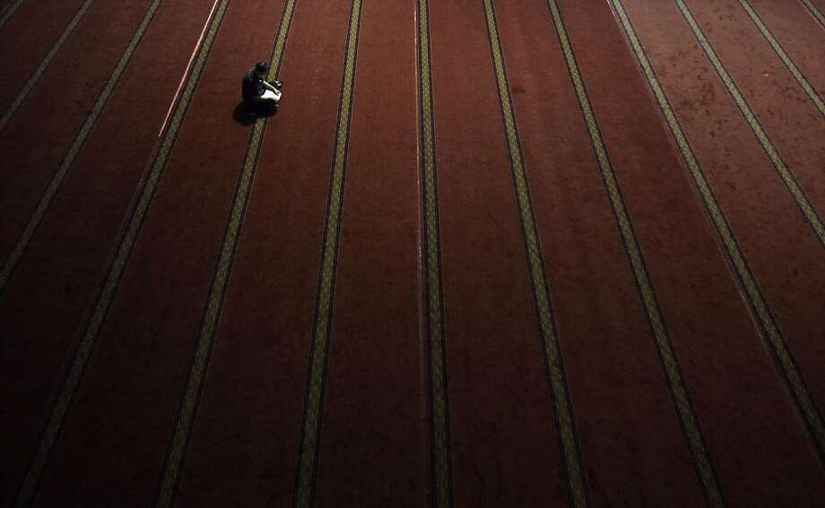 Lone worshipper: An Indonesian Muslim man reads the Quran on the first night of the holy month of Ramadan at a mosque in Jakarta. Photo: Syamsul Bahri Muhammad, Getty Images