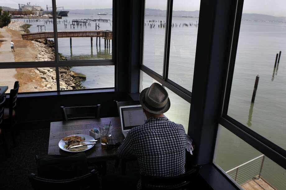 Tommy Becker from San Francisco has lunch and an iced tea while surfing the net at Mission Rock Resort.