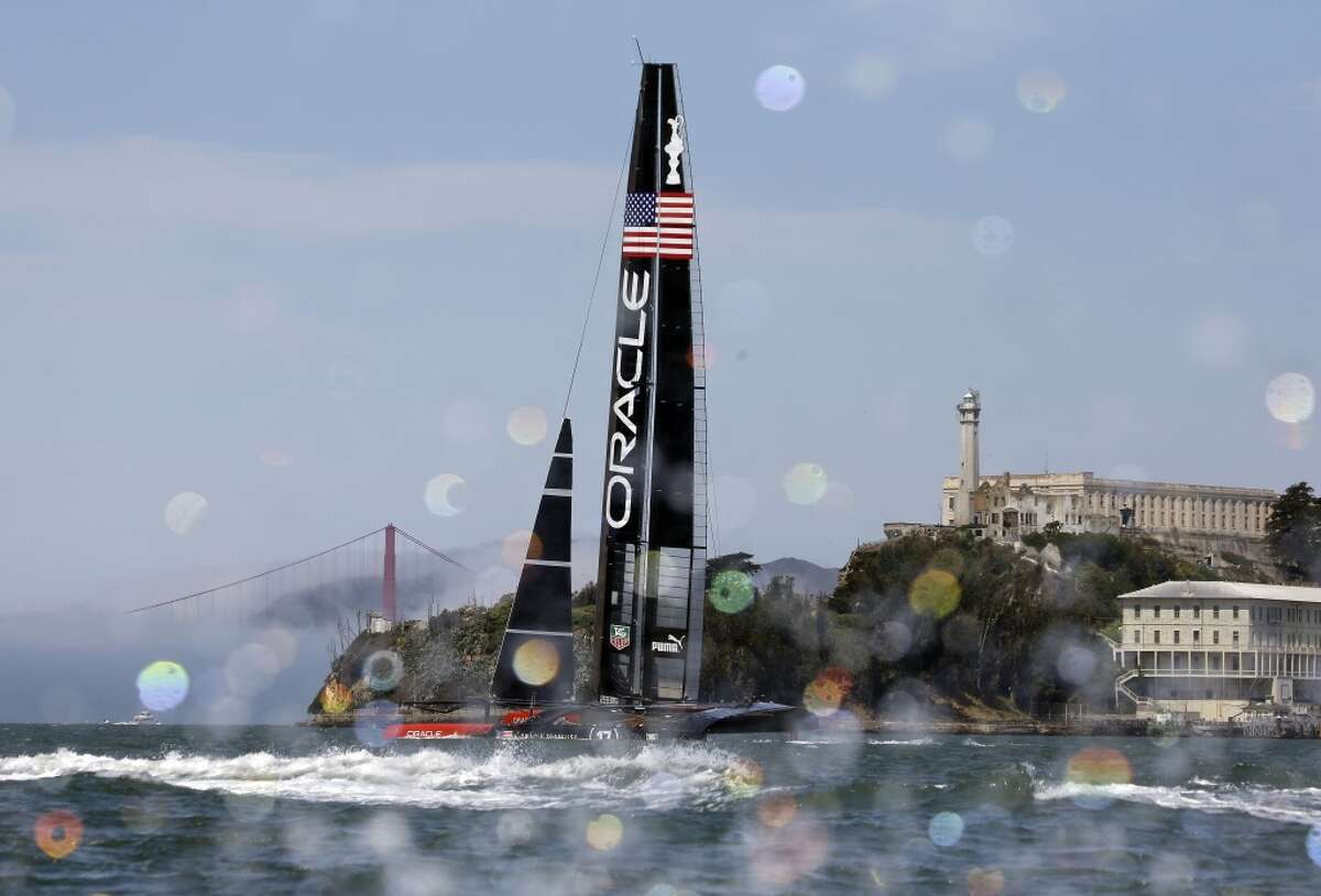 An Oracle Team USA catamaran sails past Alcatraz Island with the Golden Gate Bridge in the background during training for the America's Cup, Wednesday, July 3, 2013, in San Francisco. Opening ceremonies for the sailing event are scheduled for Thursday. (AP Photo/Eric Risberg)