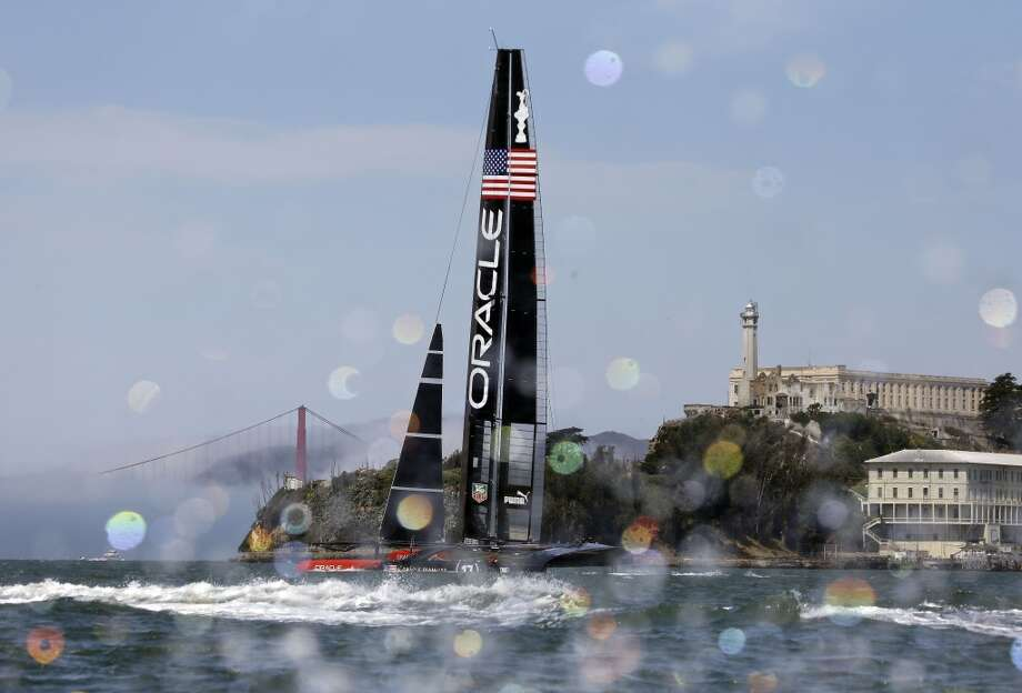 An Oracle Team USA catamaran sails past Alcatraz Island with the Golden Gate Bridge in the background during training for the America's Cup, Wednesday, July 3, 2013, in San Francisco. Opening ceremonies for the sailing event are scheduled for Thursday. (AP Photo/Eric Risberg) Photo: Associated Press