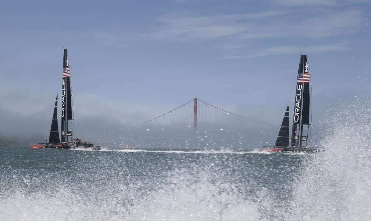 A pair of Oracle Team USA catamarans make their way past the Golden Gate Bridge in the fog during training for the America's Cup Wednesday, July 3, 2013 in San Francisco. Opening ceremonies for the sailing event are on Thursday. (AP Photo/Eric Risberg)