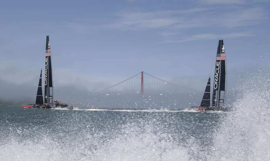 A pair of Oracle Team USA catamarans make their way past the Golden Gate Bridge in the fog during training for the America's Cup Wednesday, July 3, 2013 in San Francisco. Opening ceremonies for the sailing event are on Thursday. (AP Photo/Eric Risberg) Photo: Associated Press