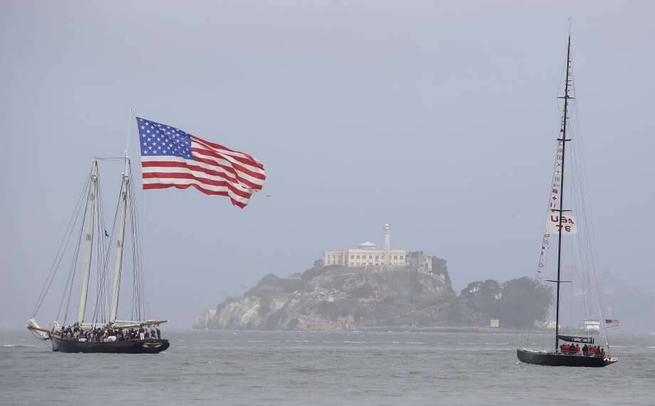 The yacht America, left, and USA 76, right, make their way past Alcatraz Island during a parade of boats for the America's Cup sailing event Friday, July 5, 2013, in San Francisco. The yacht is a replica of the original America, which in 1851 won a sailing race that now bears her name. USA 76 was used by the Oracle racing team in 2003 in New Zealand. (AP Photo/Eric Risberg) Photo: Associated Press