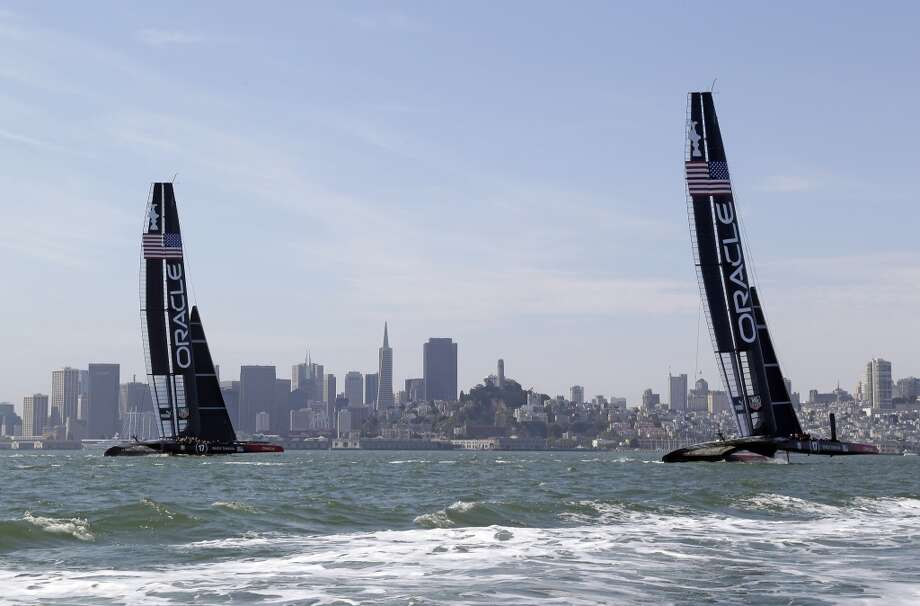 A pair of Oracle Team USA catamarans sails past the skyline during training for the America's Cup Wednesday, July 3, 2013 in San Francisco. Opening ceremonies for the sailing event are on Thursday. (AP Photo/Eric Risberg) Photo: Associated Press