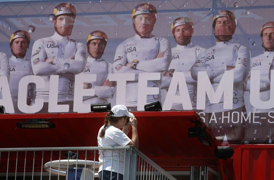 Rita Montalvan of Mill Valley takes a photo under a poster of the Oracle racing team at the newly opened America's Cup Park, in San Francisco, Calif., on Thursday July 4, 2013. America's Cup Park opens along the Embarcadero launching the first day of the summer of racing. Photo: The Chronicle