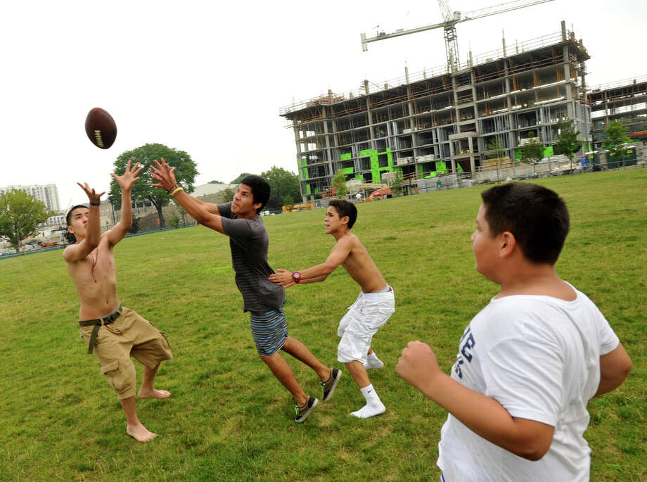 Elmer Oliva, left, and Smith Rizzo compete for the reception as Alonzo Abrego, center, and Lenny Perez, right, look on during a pick-up football game at Commons Park in Stamford on Tuesday, July 9, 2013. Photo: Jason Rearick / Stamford Advocate
