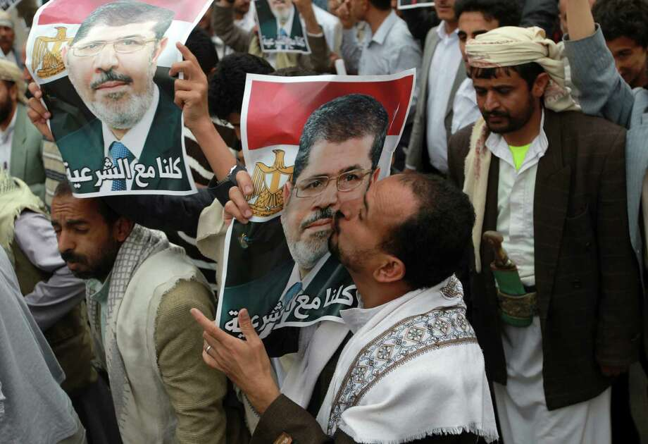 A Yemeni protestor kisses a picture of Egypt's ousted president Mohamed Morsi during a demonstration in support of the former Islamist leader in Sanaa. The United States is wise not to pick sides in the turmoil. Photo: Mohammed Huwais, Getty Images