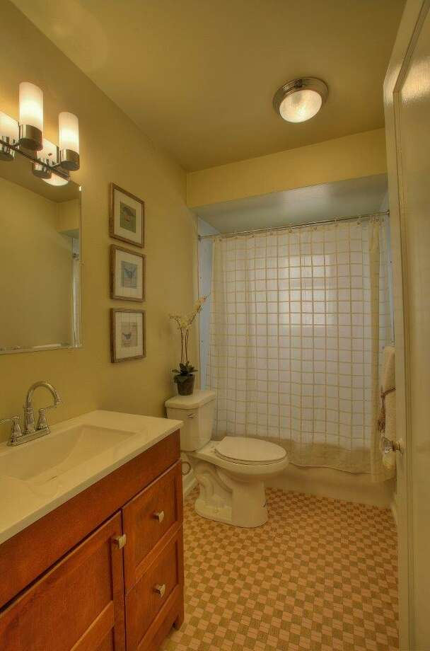 Bathroom of 8006 11th Ave. N.E. The 2,160-square-foot Tudor, built in 1929, has four bedrooms, 2.25 bathrooms, two kitchens, a family room, coved ceilings, inlaid floors and a deck on a 3,400-square-foot lot. It's listed for $468,950, although a sale is pending. Photo: Jim Arcari, Courtesy Laura Ford, Skyline Properties