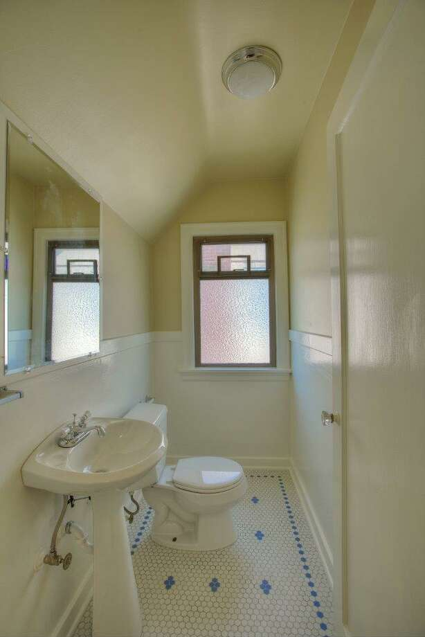 Powder room of 8006 11th Ave. N.E. The 2,160-square-foot Tudor, built in 1929, has four bedrooms, 2.25 bathrooms, two kitchens, a family room, coved ceilings, inlaid floors and a deck on a 3,400-square-foot lot. It's listed for $468,950, although a sale is pending. Photo: Jim Arcari, Courtesy Laura Ford, Skyline Properties