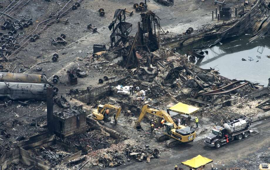 This aerial photo, workers comb through the debris after a train derailed causing explosions of railway cars carrying crude oil Tuesday, July 9, 2013 in Lac-Megantic, Quebec, Canada on Tuesday July 9, 2013.  At least thirteen people were confirmed dead and nearly 40 others were still missing in a catastrophe that raised questions about the safety of transporting oil by rail instead of pipeline.  (AP Photo/ The Canadian Press, Paul Chiasson) Photo: Associated Press