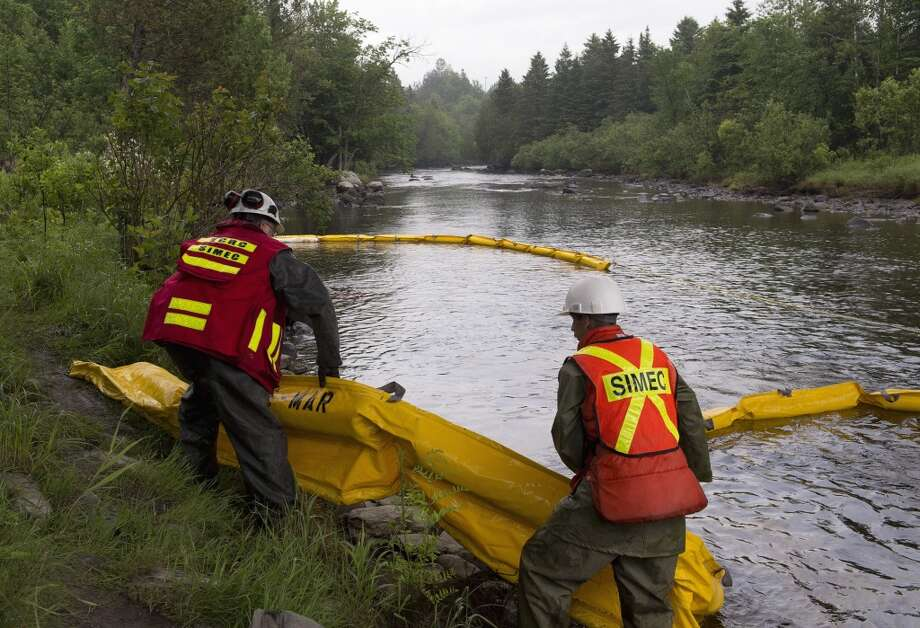 Environment workers lay booms on the Chaudiere River near Lac-Megantic, Que., to contain the crude oil spill following a train derailment and explosion, Tuesday, July 9, 2013.  At least thirteen people were confirmed dead and nearly 40 others were still missing in a catastrophe that raised questions about the safety of transporting oil by rail instead of pipeline.  (AP Photo/ The Canadian Press, Jacques Boissinot) Photo: Jacques Boissinot, Associated Press