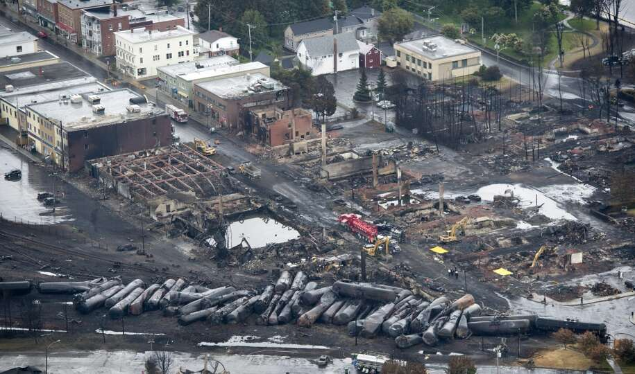This aerial photo, workers comb through the debris after a train derailed causing explosions of rail
