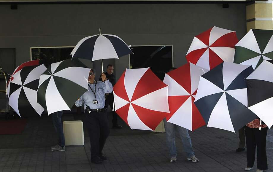 Crowne Plaza Hotel employees and others hold up umbrellas to block views of family members and survivors of the Asiana Airlines crash that are staying at the hotel in Burlingame, Calif. on Tuesday, July 9, 2013. A large curtain was later erected to block further visability. Photo: Paul Chinn, The Chronicle