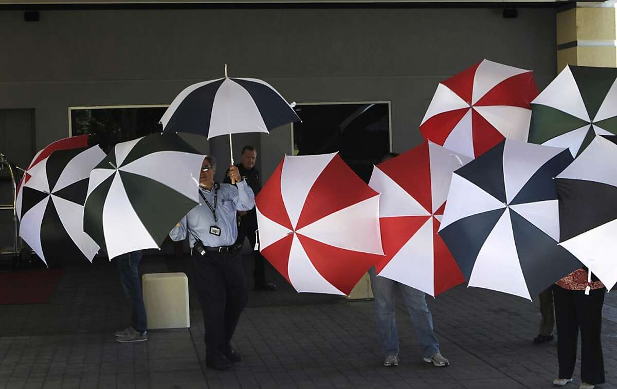 Crowne Plaza Hotel employees and others hold umbrellas to block views of family members and crash survivors staying at the Burlingame hotel.