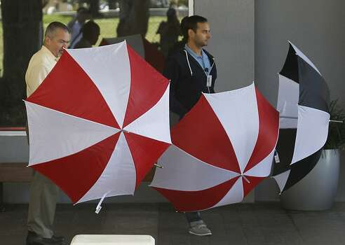 Crowne Plaza Hotel employees and others open umbrellas to block views of family members and survivors of the Asiana Airlines crash that are staying at the hotel in Burlingame, Calif. on Tuesday, July 9, 2013. A large curtain was later erected to block further visability. Photo: Paul Chinn, The Chronicle