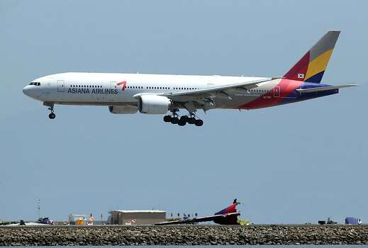 SAN FRANCISCO, CA - JULY 09:  An Asiana Airlines flight lands above wreckage from Asiana Airlines flight 214 as it sits on runway 28L at San Francisco International Airport on July 9, 2013 in San Francisco, California.  Three days after Asiana Airlines flight 214 crash landed at San Francisco International Airport, the National Transportation Safety Board (NTSB) is continuing their investigation as to why the plane crashed.  (Photo by Justin Sullivan/Getty Images) Photo: Justin Sullivan, Getty Images