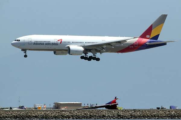 SAN FRANCISCO, CA - JULY 09:  An Asiana Airlines flight lands above wreckage from Asiana Airlines flight 214 as it sits on runway 28L at San Francisco International Airport on July 9, 2013 in San Francisco, California.  Three days after Asiana Airlines flight 214 crash landed at San Francisco International Airport, the National Transportation Safety Board (NTSB) is continuing their investigation as to why the plane crashed.  (Photo by Justin Sullivan/Getty Images)