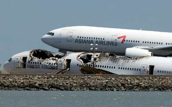 SAN FRANCISCO, CA - JULY 09:  An Asiana Airlines flight lands next to the wreckage of Asiana Airlines flight 214 as it sits on runway 28L at San Francisco International Airport on July 9, 2013 in San Francisco, California. Three days after Asiana Airlines flight 214 crash landed at San Francisco International Airport, the National Transportation Safety Board (NTSB) is continuing their investigation as to why the plane crashed.  (Photo by Justin Sullivan/Getty Images) Photo: Justin Sullivan, Getty Images