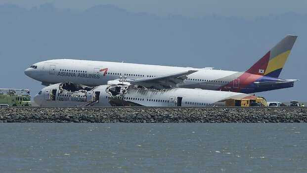 Tuesday's Asiana Flight 214 comes in for a landing over the wreckage of Saturday's Asiana Flight 214 at San Francisco International Airport in San Francisco, Tuesday, July 9, 2013. Saturday's Asiana Flight 214, crashed upon landing, two of the 307 passengers aboard were killed.,  (AP Photo/Jeff Chiu) Photo: Jeff Chiu, Associated Press