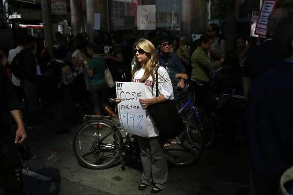 CCSF Physics Professor Jill Johnsen holds a sign during a protest against  the possibility of the revocation of the City College of San Francisco in San Francisco, Calif. on July 9, 2013.