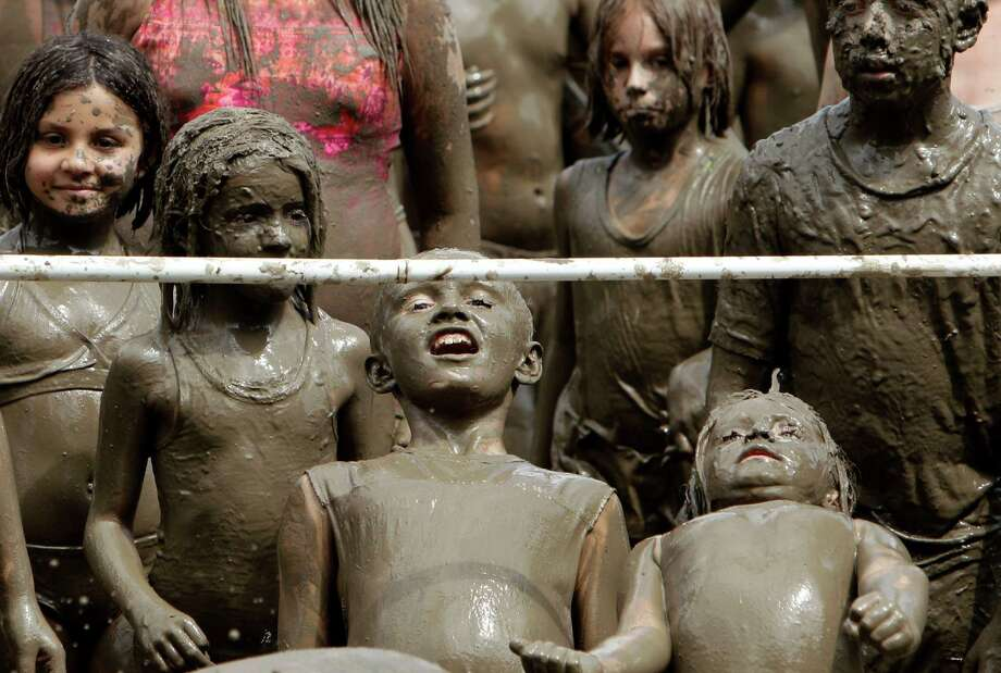 Children do the limbo in the mud in Westland, Mich., Tuesday, July 9, 2013. Hundreds of kids enjoyed the annual Mud Day event in a 7-by-150-foot mud pit. Photo: Paul Sancya, Associated Press / AP