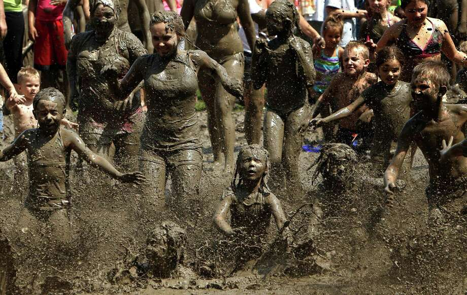 Children run into the mud in Westland, Mich., Tuesday, July 9, 2013. Hundreds of kids enjoyed the annual Mud Day event in the 7-by-150-foot mud pit. Photo: Paul Sancya, Associated Press / AP