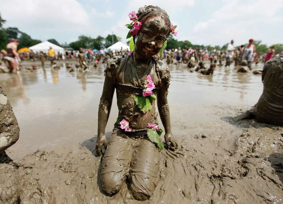 Chelsea Crayne, 9, of Riverview, wears flowers while playing in the mud in Westland, Mich., Tuesday, July 9, 2013. Hundreds of kids enjoyed the annual Mud Day event in a 7-by-150-foot mud pit. Photo: Paul Sancya, Associated Press / AP