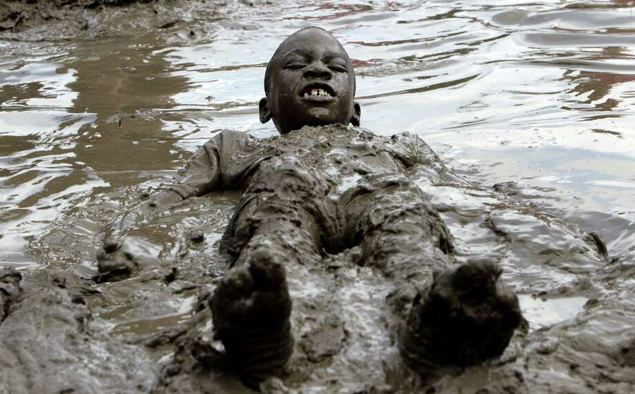 Orlando Daniels, 8, of Canton, plays in the mud in Westland, Mich., Tuesday, July 9, 2013. Hundreds of kids enjoyed the annual Mud Day event in a 7-by-150-foot mud pit. Photo: Paul Sancya, Associated Press / AP