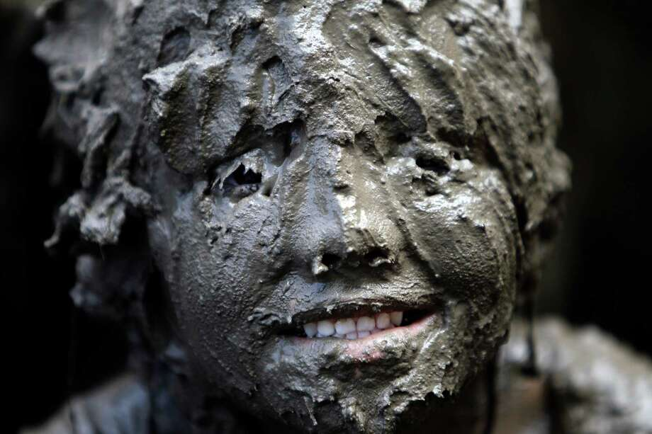 Lilli Alcala, 7, of Redford, smiles while covered in mud in Westland, Mich., Tuesday, July 9, 2013. Hundreds of kids enjoyed the annual Mud Day event in a 7-by-150-foot mud pit. Photo: Paul Sancya, Associated Press / AP