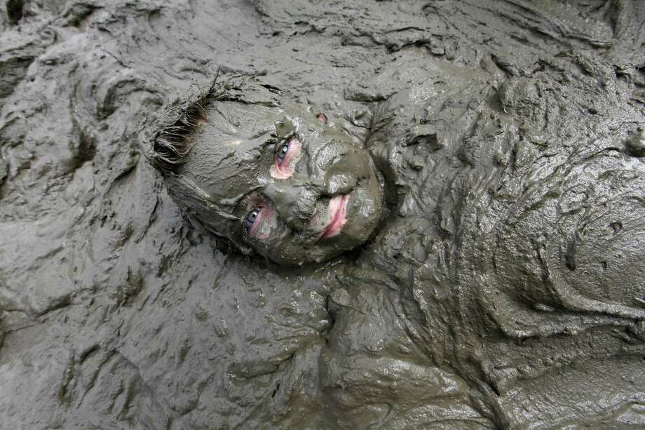 Zach Miller, 10, of Livonia lies in mud in Westland, Mich., Tuesday, July 9, 2013. Hundreds of kids enjoyed the annual Mud Day event in a 7-by-150-foot mud pit. Photo: Paul Sancya, Associated Press / AP