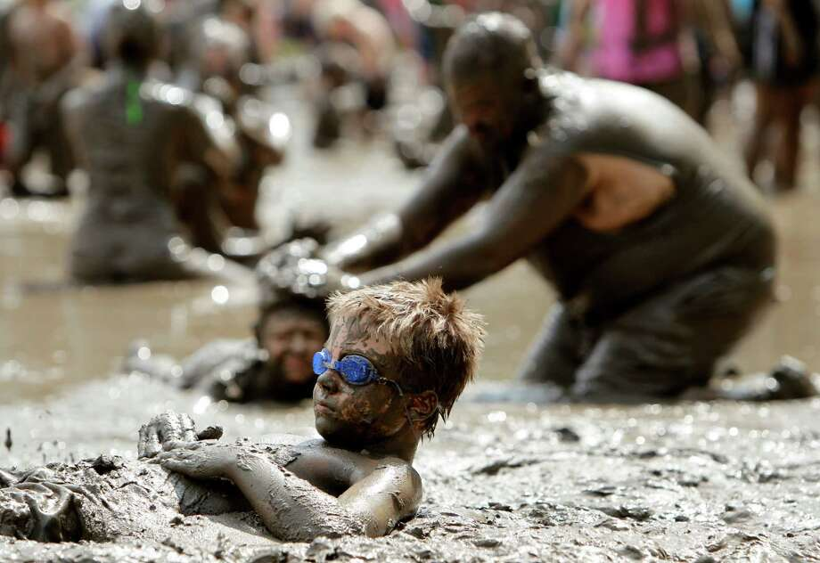 Trey Williams, 9, of Pontiac, plays in the mud in Westland, Mich., Tuesday, July 9, 2013. Hundreds of kids enjoyed the annual Mud Day event in a 7-by-150-foot mud pit. Photo: Paul Sancya, Associated Press / AP