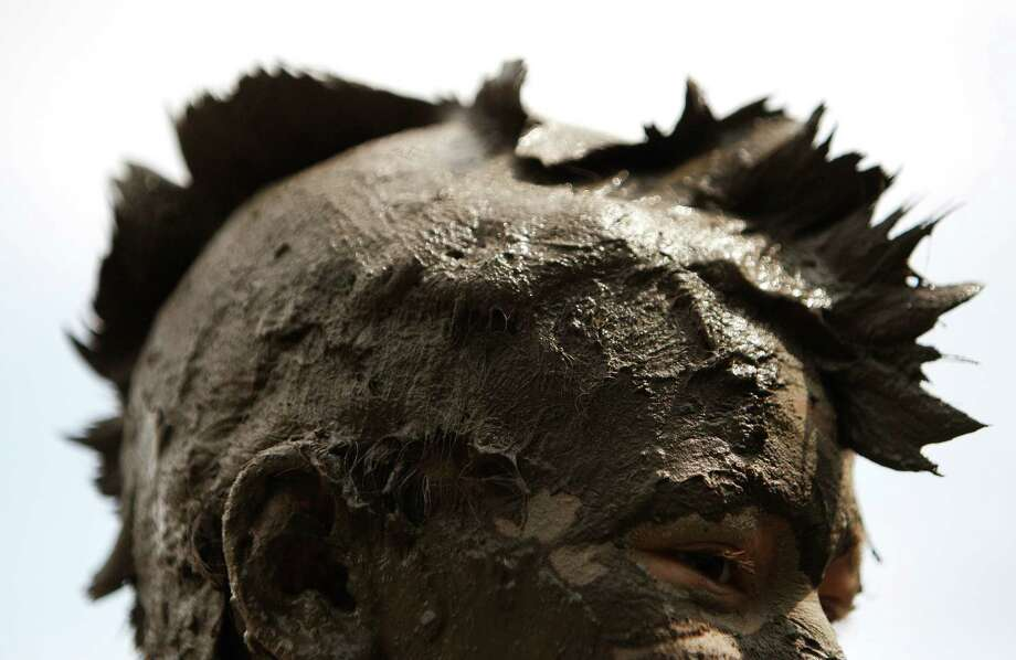 Ben Rojewski, 12, of Livonia, wears a mohawk in the mud in Westland, Mich., Tuesday, July 9, 2013. Hundreds of kids enjoyed the annual Mud Day event in a 7-by-150-foot mud pit. Photo: Paul Sancya, Associated Press / AP