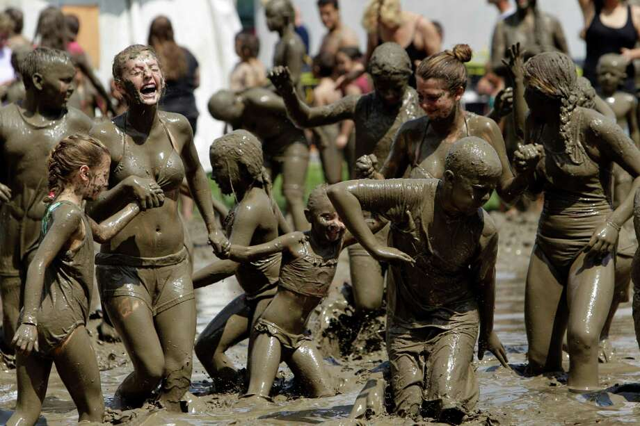 Children play in the mud in Westland, Mich., Tuesday, July 9, 2013. Hundreds of kids enjoyed the annual Mud Day event in a 7-by-150-foot mud pit. Photo: Paul Sancya, Associated Press / AP