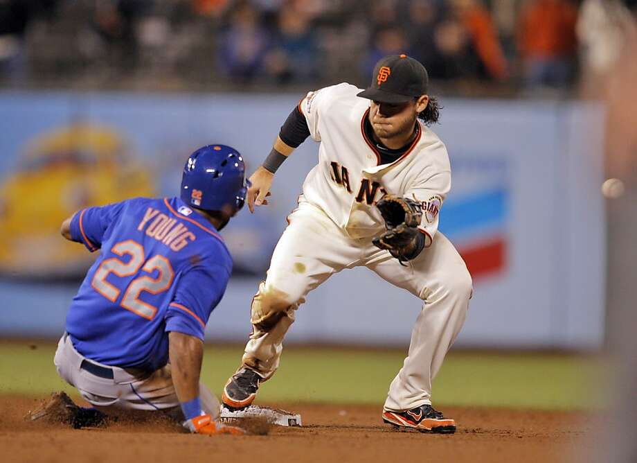 Brandon Crawford can't get a handle on a throw from Buster Posey as Eric Young steals second in the 16th inning. Photo: Carlos Avila Gonzalez, The Chronicle
