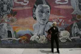 Esotouric literary crime guide actress Kelly Kuvo poses in front of a mural titled: Dolores del Rio, painted by Los Angeles artist Alfredo De Batuc, in the Hollywood area of Los Angeles, April 17, 2007. (AP Photo/Damian Dovarganes)