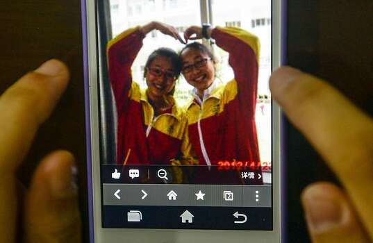 This photo taken on July 8, 2013 shows a picture of Wang Linjia (right) and Ye Mengyuan on a mobile phone, at Jiangshan Middle School in Jiangshan, east China's Zhejiang Province. Two Chinese passengers, Wang Linjia and Ye Mengyuan, were killed in a crash landing of an Asiana Airlines Boeing 777 at the San Francisco airport on Saturday morning, July 6. The two girls are both students of Jiangshan Middle School.  Photo: Han Chuanhao/Xinhua, McClatchy-Tribune News Service
