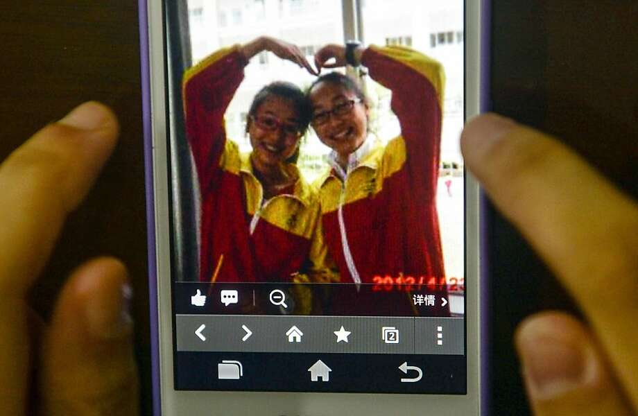 This photo taken on July 8, 2013 shows a picture of Wang Linjia (right) and Ye Mengyuan on a mobile phone, at Jiangshan Middle School in Jiangshan, east China's Zhejiang Province. Two Chinese passengers, Wang Linjia and Ye Mengyuan, were killed in a crash landing of an Asiana Airlines Boeing 777 at the San Francisco airport on Saturday morning, July 6. The two girls are both students of Jiangshan Middle School. Their family members headed for the United States on Monday. Photo: Han Chuanhao/Xinhua, McClatchy-Tribune News Service
