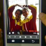 This photo taken on July 8, 2013 shows a picture of Wang Linjia (right) and Ye Mengyuan on a mobile phone, at Jiangshan Middle School in Jiangshan, east China's Zhejiang Province. Two Chinese passengers, Wang Linjia and Ye Mengyuan, were killed in a crash landing of an Asiana Airlines Boeing 777 at the San Francisco airport on Saturday morning, July 6. The two girls are both students of Jiangshan Middle School. Their family members headed for the United States on Monday.