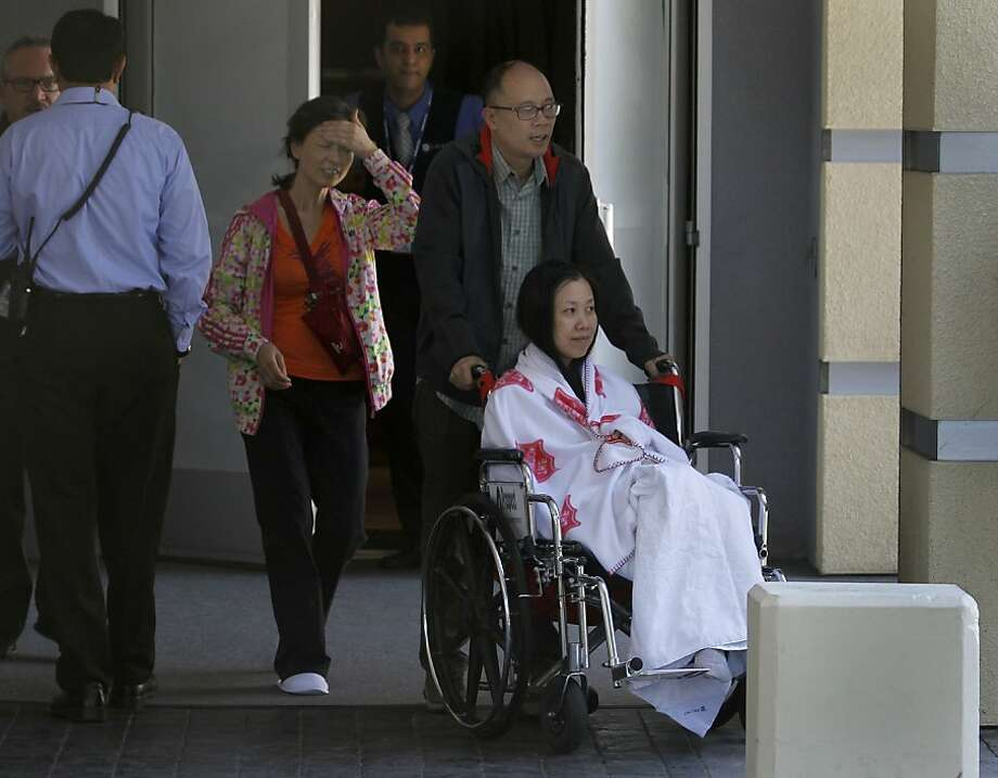 An unidentified woman in a wheelchair prepares to leave the Crowne Plaza Hotel under tight security in Burlingame, Calif. on Tuesday, July 9, 2013, where the relatives of passengers from Asiana Airlines flight 214 are reportedly staying. Photo: Paul Chinn, The Chronicle