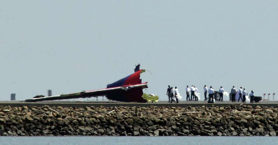 Investigators walk near the tail section of the Boeing 777 wide-body jet that crashed on a runway at San Francisco airport. Four pilots had been working Asiana Airlines Flight 214. Photo: Justin Sullivan / Getty Images