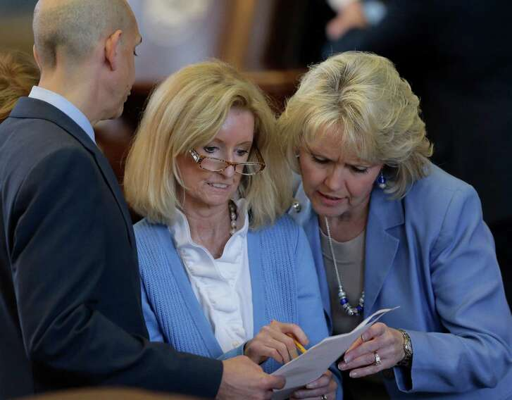 Rep. Jodie Laubenberg, R-Parker, center, and Rep. Cindy Burkett, R-Garland, right, talk  as HB 2, legislation that will restrict abortion rights,  is debated on the Texas House floor,Tuesday, July 9, 2013, in Austin, Texas. The Texas House is expected to vote on the bill Tuesday. (AP Photo/Eric Gay)