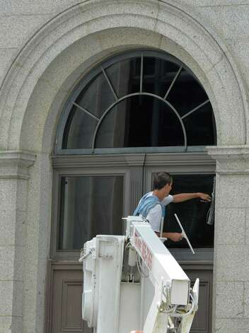 A window washer cleans the windows July 9, 2013, on the north end of the SUNY complex in Albany, N.Y.        ( Skip Dickstein/Times Union ) Photo: Skip Dickstein