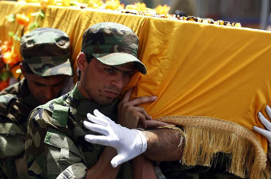 Members of Iraq's Hezbollah Brigades carry the coffin of a Shiite fighter, Hameed Abdul-Hassan al-Missari, during the funeral procession in Baghdad, Iraq, Tuesday, July 9, 2013. Hundreds of Iraqis have mourned in Baghdad a Shiite fighter killed in Syria, a spokesman for Iraq's Hezbollah Brigades which has been sending fighters to Syria to fight alongside President Bashar Assad's troops, said Monday that the 50-year old Hameed Abdul-Hassan al-Missari was killed three days ago. (AP Photo/Karim Kadim) Photo: Karim Kadim, Associated Press